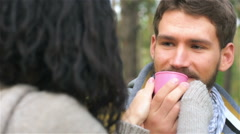 Young girl gives to drink some tea from cup her boyfriend Stock Footage