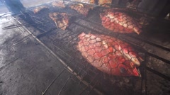 Fresh-caught tuna and red snapper cooking on grill BBQ on the fire by fisherman Stock Footage