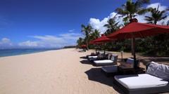 Rows of deck chairs on a beach. Coast near hotel. Daytime. Nusa Dua beach Stock Footage