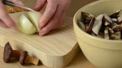 Woman is cutting fresh onion into pieces, creating bay bolete mushroom meal Stock Footage