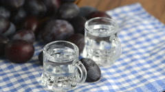 Plum liquor in two small glasses. in background rolling fresh plums around. Stock Footage