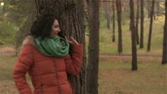Flirty girl hiding behind tree from her boyfriend Stock Footage