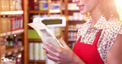 Female staff looking at a grocery item at payment counter Stock Footage