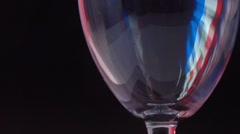 Pouring red wine into glass against black background with French flag-like Stock Footage