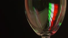 Pouring red wine into glass against black background with Italian flag highlight Stock Footage