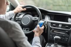 Man using a smartphone and driving Kuvituskuvat