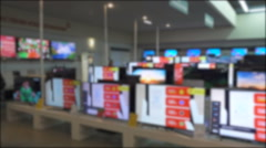 Many flat tv sets stay working on showcase in shop, Out of focus background Stock Footage
