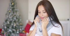 Dreamy young woman snuggling into her scarf Stock Footage