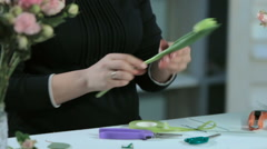 Florist cuts tape ribbon a flower tulip on a white table Stock Footage