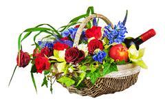 Flower arrangement of roses, orchids, fruits and bottle of wine in basket iso Kuvituskuvat