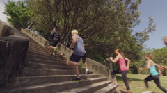 Group of people outdoor fitness training running up staircase in a park Stock Footage
