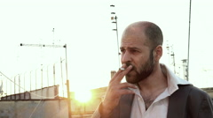 Anxiuos man looks around nervously while smoking a cigarette Stock Footage