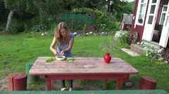 Villager blond girl pod green peas on wooden table near rural house. 4K Stock Footage