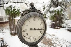 Clock on the snowy background Stock Photos