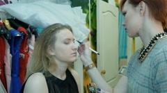 Professional makeup artist applies makeup to a beautiful model Stock Footage