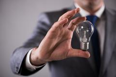 Businessman holding light bulb in creativity concept Stock Photos