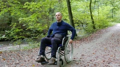 Disabled man in a wheelchair in a forest park Stock Footage