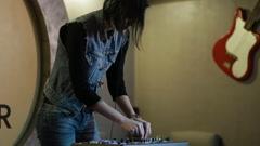 Woman DJ tweak different track controls on dj's deck at nightclub Stock Footage