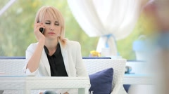 Woman talking on cell phone and looking magazine. Stock Footage