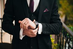Groom clasping stylish watch band on his wrist Stock Photos