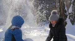 Girl and child throwing snow over himself and enjoys it in the winter park Stock Footage