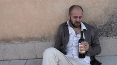 Drunk businessman lying on the ground, crying drinking a bottle of wine Stock Footage