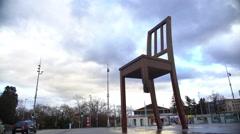 Broken Chair memorial near Palace of Nations, tourists taking photos, panorama Stock Footage