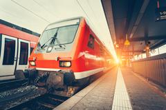 Modern high speed red commuter train at colorful sunset Stock Photos