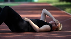 Tired girl resting after Jogging on the floor at the stadium Stock Footage