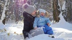 A girl with a child playing with snow in the park in a Sunny day Stock Footage