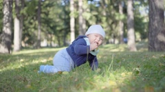 Baby crawls on the grass and eats leaves, smiling and playing Stock Footage