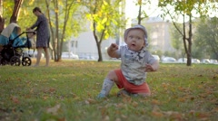 Baby in panama furious, waving his arms and crawling. Park outdoor Stock Footage