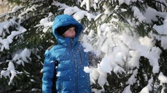 Teen throws off snow from tree branches in a sunny day Stock Footage