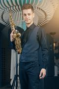 Young man in a suit standing with saxophone Kuvituskuvat