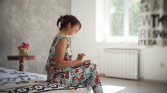 Cute girl looking at the tablet in the room with sunlight Stock Footage