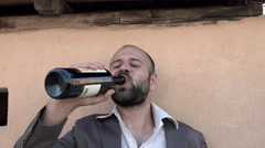 Elegant man gets drunk with wine bottle Stock Footage