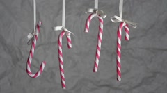 Candy Canes hanging on a ribbon on a background of crumpled wrapping paper. Stock Footage