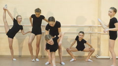 A group of girls stretching on a barre during a ballet lesson for dance class Stock Footage
