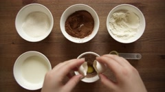 The girl mixes future cake in a cup. The girl adds egg to mix for cake Stock Footage