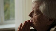 Portrait of elderly praying woman Stock Footage
