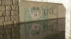Concrete bridge with grafiti reflected in rippling water with dappled sunligh Stock Footage