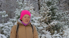 Young woman meditates in a snowy winter forest during snowfall Stock Footage