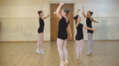 Closeup of a group of young girls and a dance teacher learning ballet in a dance Arkistovideo