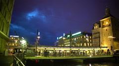 Urban life, passengers entering modern tram, brightly illuminated city center Stock Footage