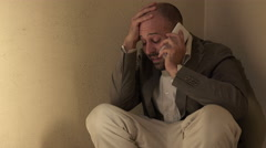man desperate cries talking on the phone crouching on the floor Stock Footage