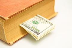 Hundred dollar bills in book Stock Photos