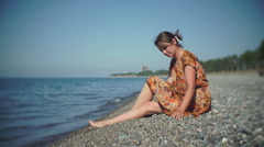Cute girl sitting on the shore throwing pebbles into the sea Stock Footage