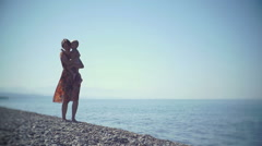 Young mother with a baby in their hands walking on the beach. The baby is Stock Footage