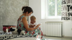 Young mother with a baby look at the tablet and smiles in the room with sun Stock Footage