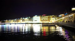 Beautiful Geneva lake at night, reflections in water, people walk on embalmment Stock Footage